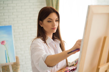 Сute girl artist paints on canvas painting on the easel. Model in the studio