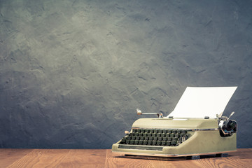 Retro typewriter with sheet of paper on wooden table front black concrete wall background. Vintage style filtered photo