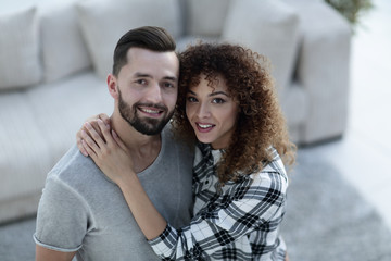 young couple standing in new living room and looking at camera