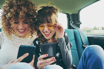 Dos amigas usando sus teléfonos móviles mientras hacen un viaje en coche