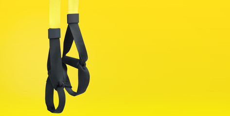 Straps training loop equipment. Black loop functional training equipment on yellow background. Sport accessories. Fitness and Gym workout items for Healthy.