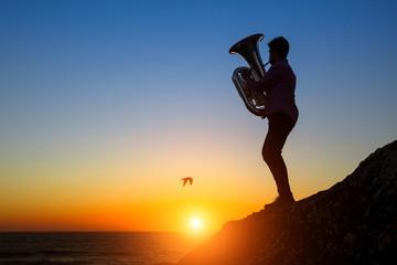 Musician play Tuba on the ocean coast at sunset.