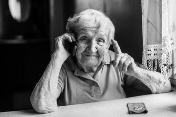 Elderly woman talks on a mobile phone.