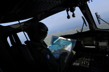 The Irish Army pilot looks at a map on the helicopter carring the polling box for the referendum on abortion law a day early for the few people that live off the coast of Donegal on the island of Inishbofin
