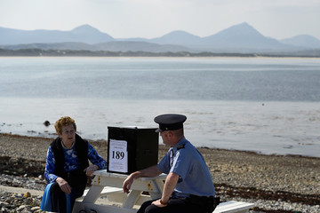 Garda Alan Gallagher and Presiding Officer Carmel McBride carry the polling box for the referendum on abortion law a day early for the few people that live off the coast of Donegal on the island of Inishbofin