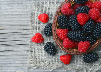 Freshly picked organic blackberries and raspberries in a basket on old wooden table.Healthy eating,vegan food or diet concept.Selective focus.