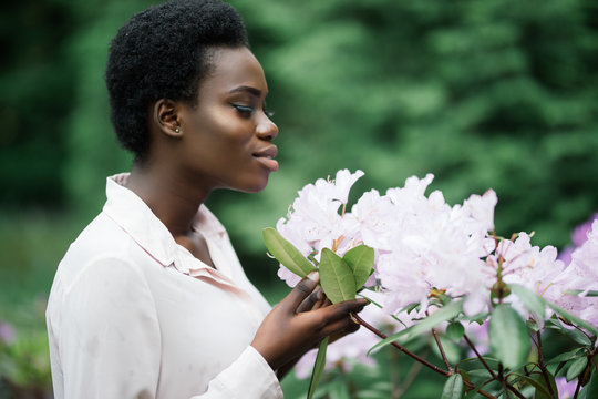 Portrait of an attractive afro american woman smelling a flower in park