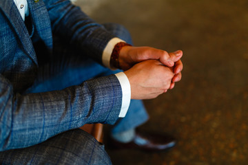 Man in a suit sits with his hands on his knees. Putting your hands together. Shoot of a man in a suit sitting with his hands folded together with space for text. Business concept. Man in his thoughts.