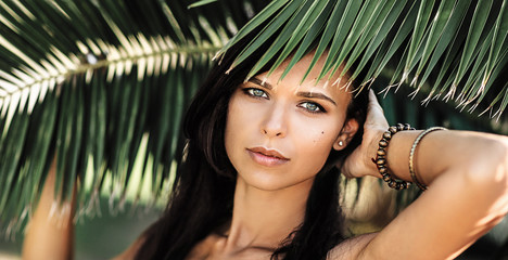 Portrait of a beautiful woman in palm leaves