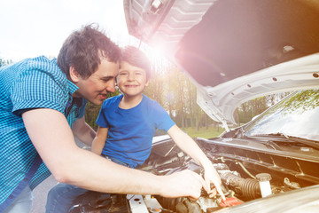 Young father teaching his little son repairing car