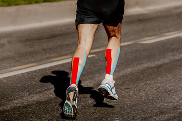 Fototapete - legs runner with kinesio tape on calf muscle running street