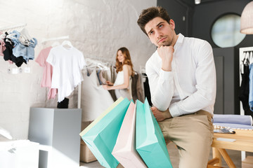 Bored man sitting and holding shopping bags