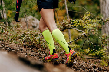 Wall Mural - female runner in yellow compression socks running forest trail