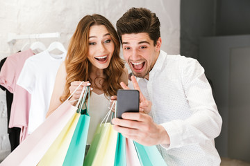 Cheerful young couple shopping for clothes together