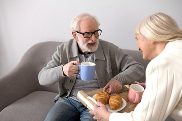 Old lady with gray hair offering her husband some hot drinks and croissants for morning meal. Aged grandpa with gray hair drinkning coffee brought by his wife in living room.