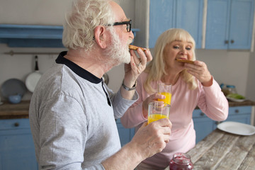 Aged married couple having meal in morning. Elderly grayhaired man enjoying some jelly toasts and orange juice with his wife for breakfast in their house.