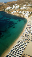 Aerial drone bird's eye view photo of famous organized with sun beds emerald clear water beach of Ornos in island of Mykonos, Cyclades, Greece