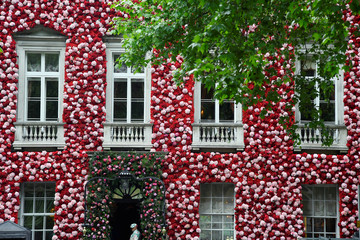 A doorman dressed in floral pattern suit stands on duty outside of Annabel's private members club, adorned with thousands of flowers, timed to coincide with the RHS Chelsea Flower Show, in Mayfair in London, Britain