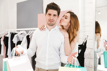 Attractive young couple standing at the clothing store
