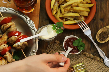 fried chicken meat on wooden sticks. hand of a young man. food background