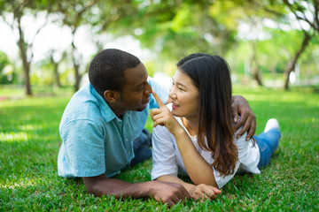 Portrait of happy young couple lying on grass and flirting
