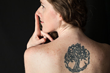 Portrait of a girl with tattoo. Back view