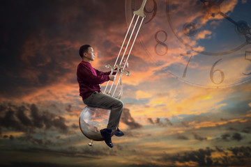Man in red sweater sitting on the pendulum of a grandfather clock which is swinging in the air on twilight background