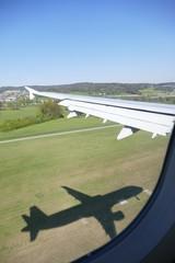 Flugzeug mit seinem Schatten bei der Landung