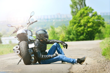 Biker in outfit sits next to his motorcycle on the ground. Motorcyclist rests near the motorbike