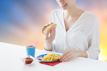 fast food and people concept - close up of happy woman eating hot dog and french fries with lemonade in paper cup over evening sky background