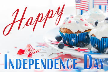 independence day, celebration, patriotism and holidays concept - close up of glazed cupcakes or muffins decorated with american flags and blueberries at party 4th of july