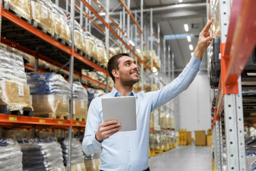 logistic business, technology and shipment concept - happy businessman with tablet pc computer checking goods at warehouse