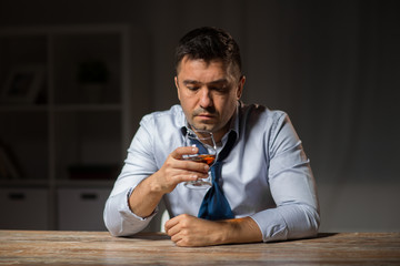 alcoholism, alcohol addiction and people concept - male alcoholic drinking brandy on table at night