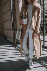 Girl with a cup of coffee, in a beige coat and white jeans