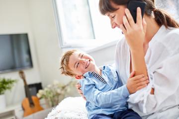 Fröhlicher Junge albert mit der Mutter herum