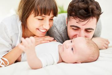 Stolze Eltern kuscheln mit ihrem Baby