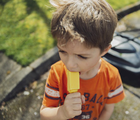 High angle view of boy eating popsicle while standing on road