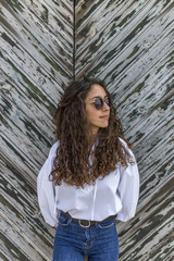 Woman wearing sunglasses while standing by wooden wall