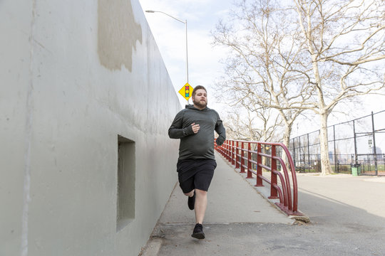 Full length of overweight man jogging in city