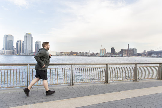 Full length of overweight man jogging on bridge by river in city