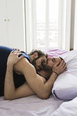 Romantic gay couple sleeping on bed at home
