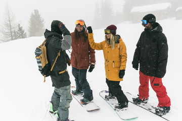 Full length of cheerful friends standing with snowboards on snow during snowfall