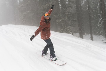 Full length of cheerful woman with arms outstretched snowboarding on snow