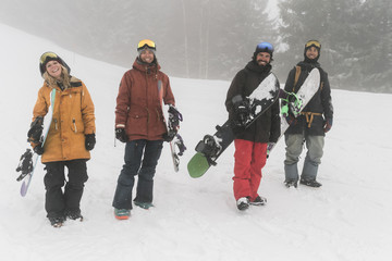 Portrait of friends with snowboards standing on snow during foggy weather