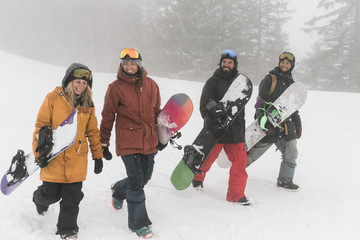 Full length of smiling friends with snowboards walking on snow during foggy weather