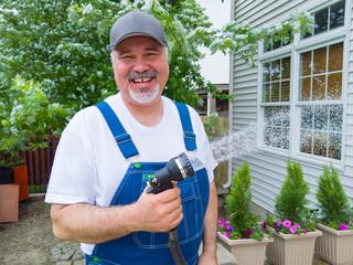 Laughing happy man watering his garden