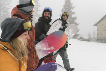 Cheerful friends with snowboards walking on snow during foggy weather