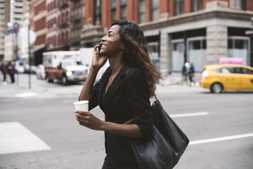 Businesswoman with coffee talking on smart phone while walking on city street
