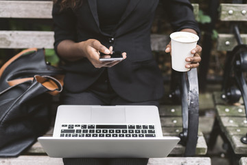 Midsection of businesswoman using smart phone while sitting with laptop computer on bench in city