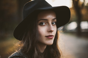 Close-up portrait of woman wearing hat while sitting at park during sunset